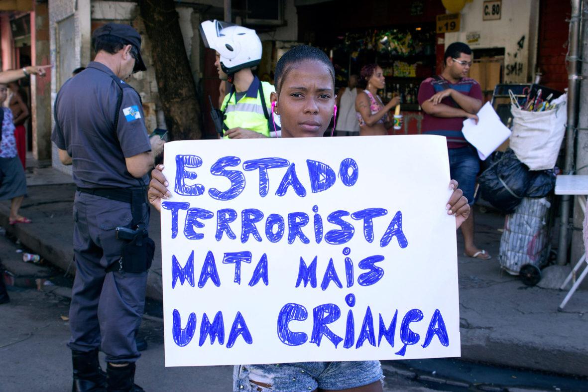 Moradora carrega cartaz denunciando a violência do Estado — Foto Rafael Daguerre