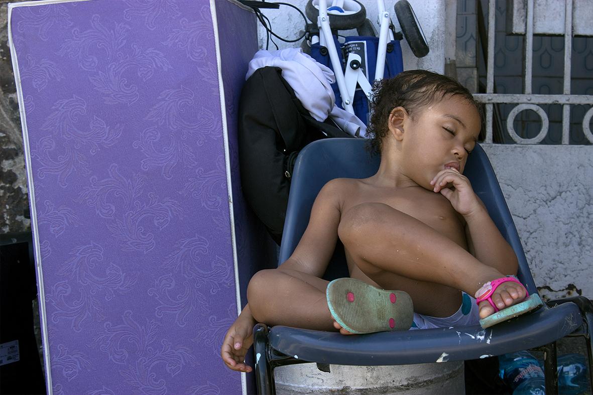 Criança dorme enquanto os pais retiram as coisas de casa — Foto: Rafael Daguerre