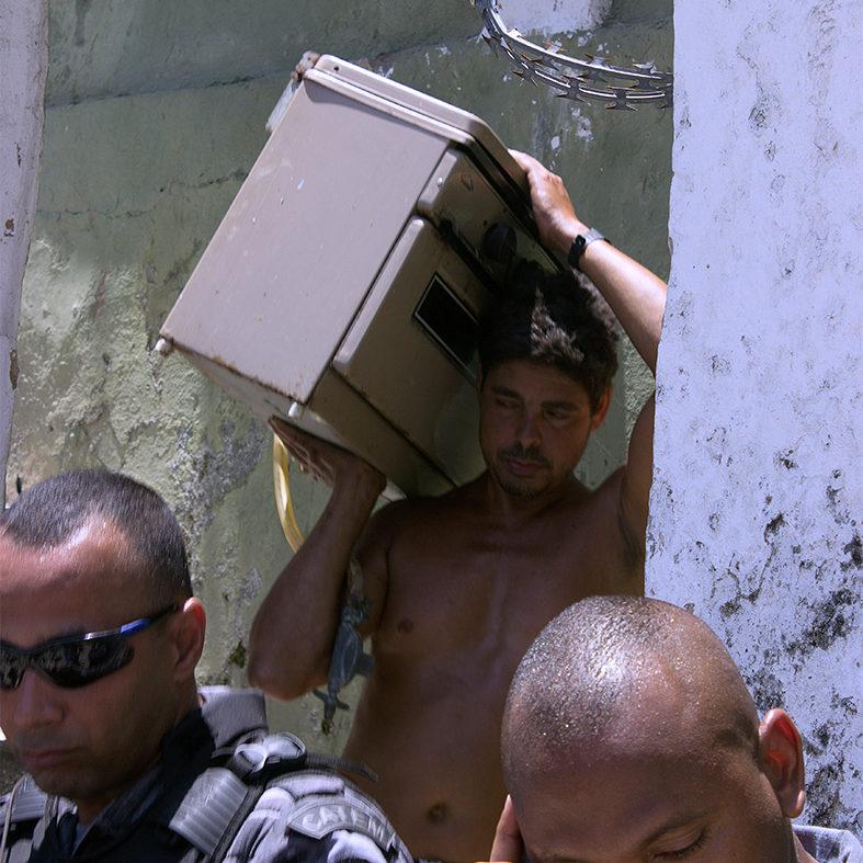 Morador carrega fogão e PMs garantem despejo forçado — Foto: Rafael Daguerre