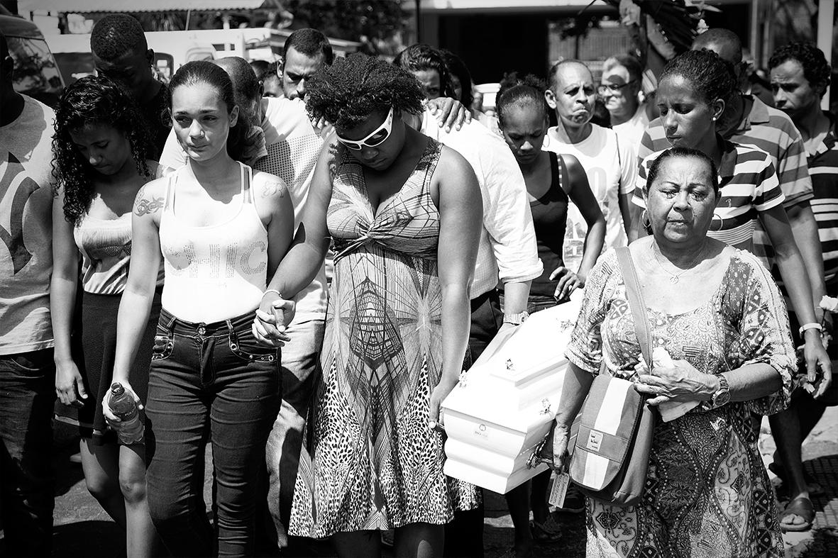 A mãe, Grabriela Gomes, carrega o caixão de seu filho durante o enterro, no Cemitério do Catumbi, zona norte do Rio de Janeiro, 13 de dezembro de 2015 — Foto: Rafael Daguerre